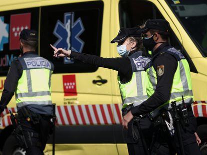 Tres agentes de policía, frente a una ambulancia.