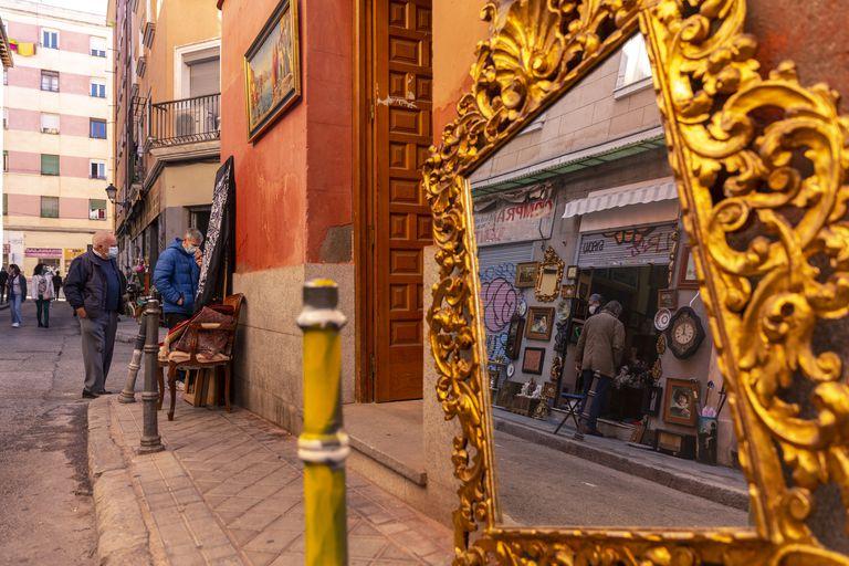 Un espejo colocado delante de unos los comercios del Rastro, este domingo por la mañana.