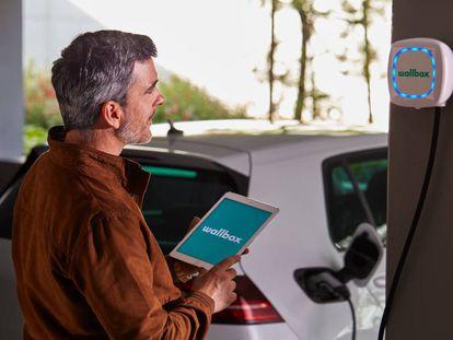 Un usuario carga su vehículo eléctrico con un dispositivo de Wallbox.