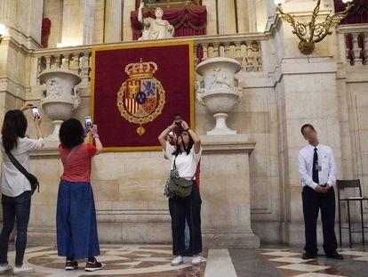 Un auxiliar de sala en el Palacio Real, junto a varias turistas.