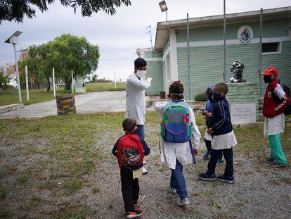 Un maestro saluda a sus alumnos en una escuela rural tras un mes de baja por la covid-19 en San José, Uruguay.