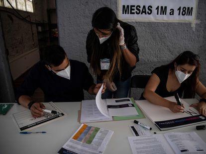 Funcionarios electorales preparan una mesa de votación en Santiago de Chile para el referéndum constitucional de este domingo.