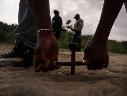 Un hombre entierra una varilla para buscar cuerpos en Colinas de Santa Fe, Veracruz.