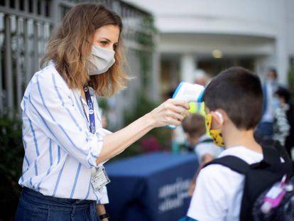 Una trabajadora toma la temperatura a un niño a la entrada del colegio privado internacional American School of Barcelona.