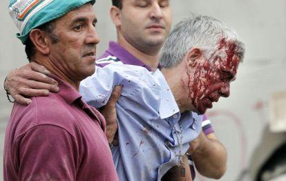 El maquinista Francisco José Garzón es ayudado por dos vecinos de Angrois tras el accidente.