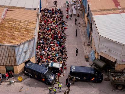 Menores extranjeros no acompañados, a las puertas de una nave usada como albergue provisional en Ceuta, el miércoles.