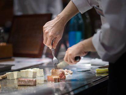 Un chef prepara carne de res al estilo teppanyaki.