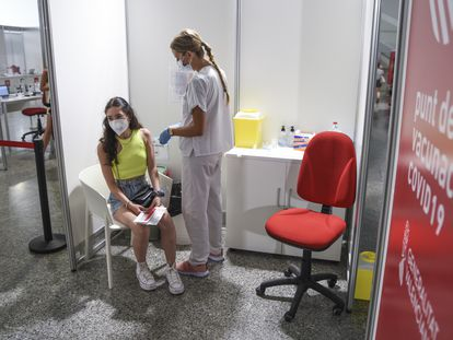 Una sanitaria vacuna a una adolescente con la primera dosis de Moderna, este lunes en la Ciudad de las Artes de Valencia.