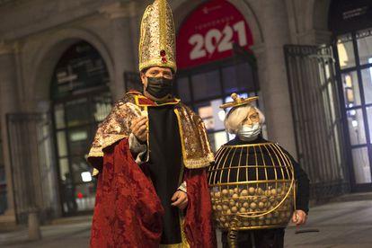 Juan Manuel López y Manoli, disfrazados de obispio y bombo, ante las puertas del Teatro Real de Madrid, este martes.