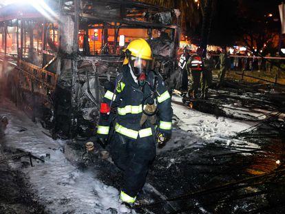 Personal de los servicios de emergencia israelíes alrededor de un autobús quemado en la ciudad de Jolón, cerca de Tel Aviv, el 11 de mayo de 2021, tras el lanzamiento de cohetes hacia Israel desde la Franja de Gaza, controlada por el movimiento palestino Hamás.