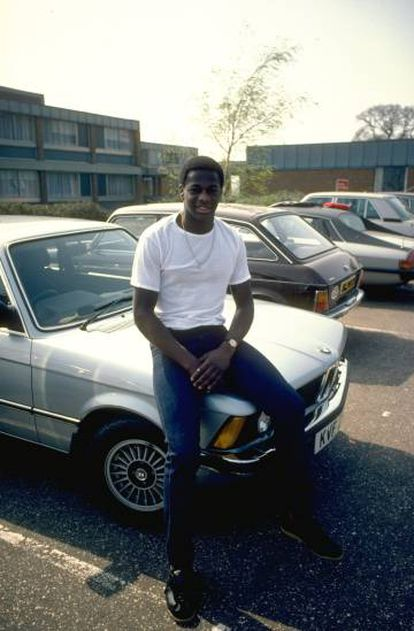 Justin Fashanu fotografiado sentado sobre el capó de su coche en 1981.