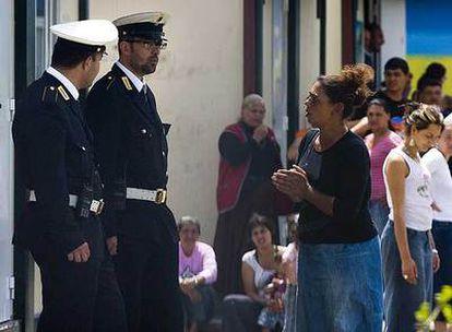 Policías locales hablan con una mujer en el campamento gitano de Il Salone, a las afueras de Roma.