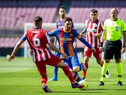 Messi, capitán del Barcelona, intenta regatear a Koke, capitán del Atlético de Madrid, durante un partido entre los dos equipos.