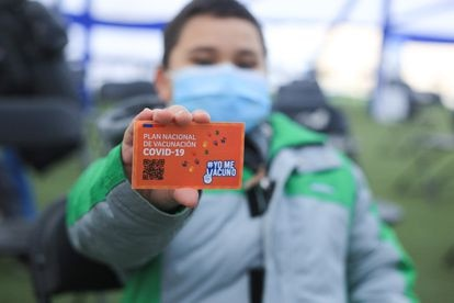 A child shows his certificate of vaccination against covid in Santiago de Chile.
