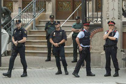Miembros de la Guardia Civil, de la Policía Nacional y de los Mossos d'esquadra en la puerta de la Delegación del Gobierno en Barcelona.