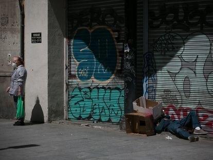 Una persona sin hogar duerme en la plaza del Pedró, en el casco antiguo de Barcelona.