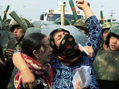 Mujeres de la minoría uigur rodeadas por policías chinos en Urumqi, durante los disturbios de julio de 2019.
