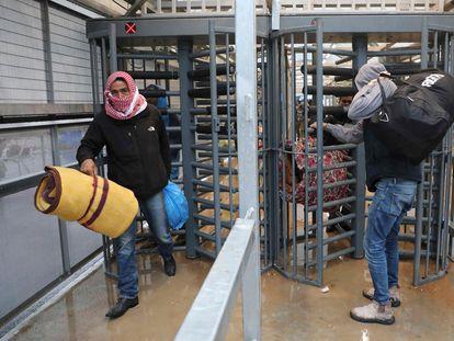 Trabajadores palestinos pasan por un puesto de control a Israel donde van a residir durante un mes, el pasado miércoles.