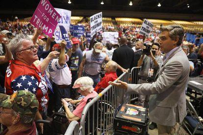 El periodista de CNN Jim Acosta habla con algunas de las personas que le abucheaban en un mitin de Trump el martes en Tampa (Florida)