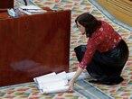 La presidenta de la Comunidad de Madrid, Isabel Díaz Ayuso, recoge del suelo papeles con las supuestas intervenciones de su Gobierno en las residencias de Madrid, el 11 de junio en la Asamblea regional.