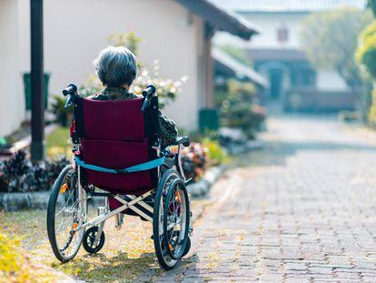 Una mujer, sentada en su silla de ruedas.