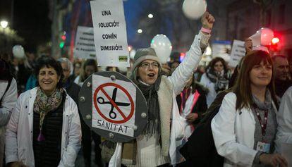 Una manifestante sostiene un cartel pidiendo la dimisión del consejero de salud, Toni Comin.