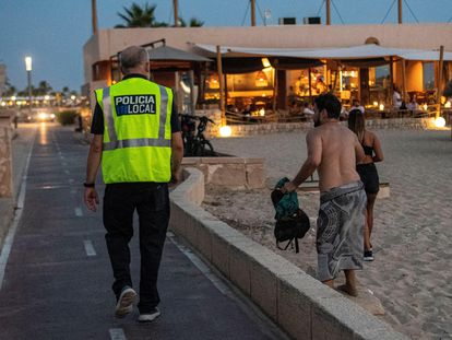 Un agente de la policía hace labores de control en una playa en Palma.