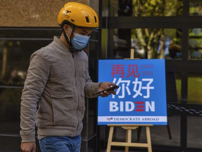 Un repartidor pasa delante de un bar en Shanghái donde se ha seguido el recuento de las elecciones de EE UU.