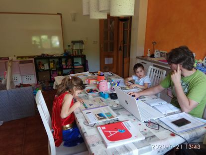 El profesor del IES Vega de Toranzo, Pablo Blanco, con sus hijas, en su salón, convertido en aula para la cuarentena.