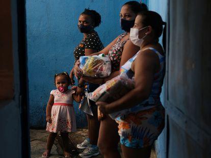 Vecinas de una favela de Río de Janeiro, tras recibir donaciones en una escuela de samba este jueves.