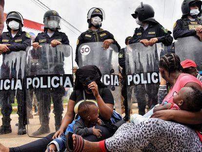 Dos madres migrantes frente al bloqueo de la policía en la localidad peruana de Iñapari, en la frontera con Brasil, este jueves.