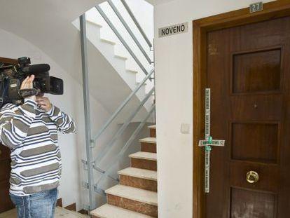 Un cámara graba ante la puerta de la vivienda de Oliva en la que un hombre ha matado a su pareja.