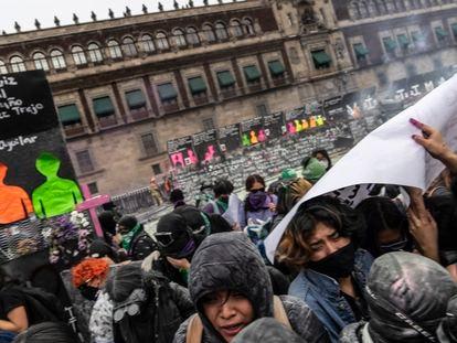 Manifestantes buscan refugio tras recibir gases lacrimógenos a las afueras de Palacio Nacional este 8-M en Ciudad de México.