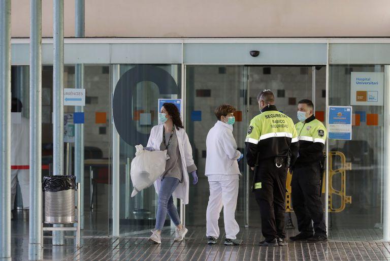 Dos agentes de seguridad junto a dos enfermeras en la entrada principal del Hospital del Mar de Barcelona. EFE / Andreu Dalmau