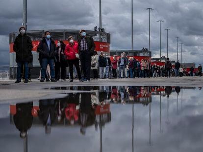 Cientos de personas hacen cola para ponerse la vacuna contra la covid-19 en el estadio Wanda Metropolitano de Madrid, este viernes.