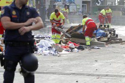 Los servicios de limpieza municipales retiran los restos del punto de información el 15-M en la Puerta del Sol.