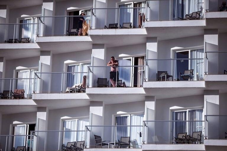 Varios turistas toman el sol en los balcones de un hotel de Torremolinos, en la Costa del Sol.