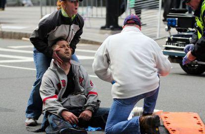 Uno de los heridos es atendido en la calle.