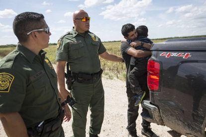 Un migrante abraza a su hijo al momento de ser detenido por la Patrulla de la Frontera en Roma, Texas