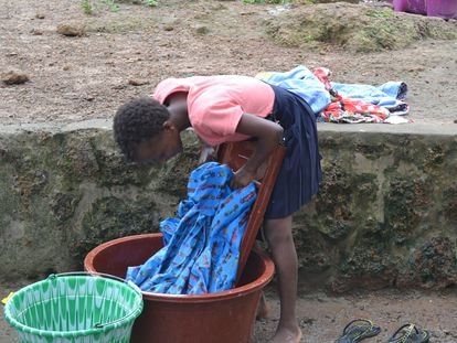 Lucy, una niña a la que se llevaron de su pueblo bajo la promesa de una mejor educación para convertirla en una esclava, lava su ropa en el refugio salesiano de la ONG Don Bosco Fambul, en Freetown.