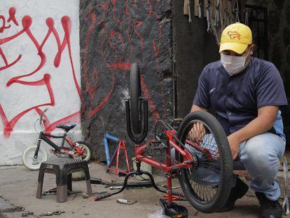 Jhoan Martín Machado repara una bicicleta en las calles de Quito (Ecuador), uno de los trabajos informales que realiza desde que llegara al país.