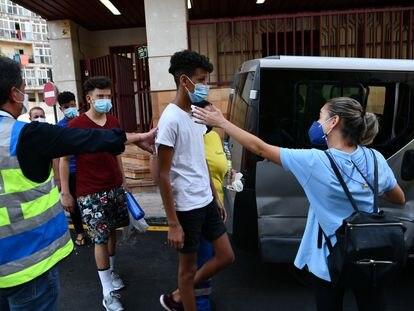 Trabajadores ayudan a tres de los menores marroquíes a las puertas del juzgado tras presentar una denuncia solicitando 'habeas corpus' minutos antes de ser repatriados a su país de origen.