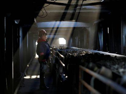 Un trabajador vigila una cadena en una planta de carbón en la provincia de Shanxi, China.