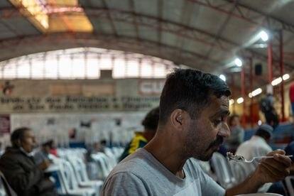 Jocelino da Silva recibe una ración de comida de una organización social.