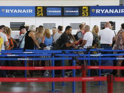 Decenas de viajeros hacen cola en el aeropuerto de Alicante en los mostradores de embarque de la compañía Ryanair.