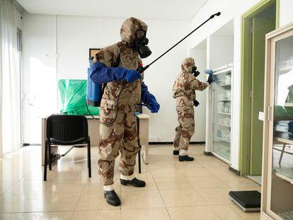 Efectivos del Ejército de Tierra, con trajes NBQ como el que soldado Vequia tuvo que ponerse para correr, realizan labores de desinfección en abril del año pasado en Canarias.