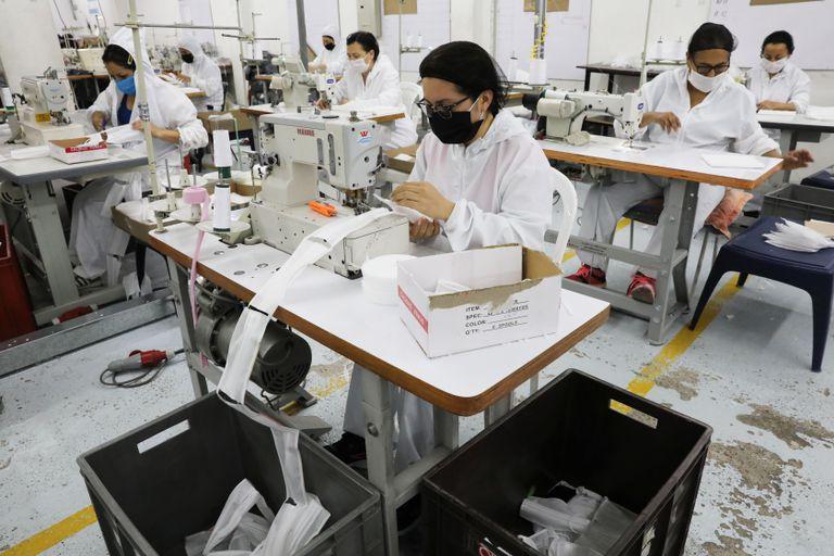 Trabajadoras de una empresa de ropa infantil fabrican mascarillas en Bogotá.