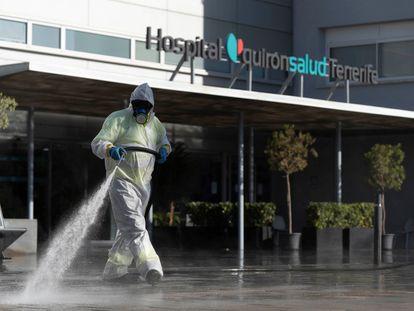 Un operario del servicio de limpieza en Santa Cruz de Tenerife desinfecta el exterior de un hospital de Quirónsalud.