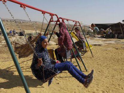 Unos niños palestinos se columpian en Susya el martes.