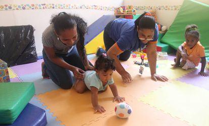 Una madre juega con su hija pequeña ante la mirada de la mayor y con la ayuda de una experta, en un centro de atención a la primera infancia en Boca Chica.